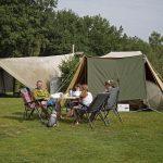 Een gezin aan de campingtafel voor de tent.