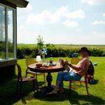 Een man op een terras in het gras voor een chalet