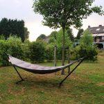 Een hangmat op standaard op het gras met een boom ernaast.