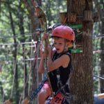 Een jongetje met rode helm aan een kabel in het bos