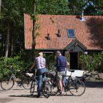 Twee fietsers staan voor De Boshut te wachten.