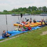 Scholieren in fel gekleurde kano's langs de waterkant