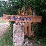 Een houten bord met hierop De Wildernis, bij de ingang van het kampeerterrein.