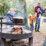 Een brandende vuurschaal met theepot erboven en een gezin eromheen.