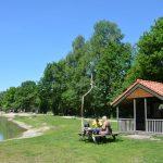 Een houten trekkershut met daarvoor een picknickbank aan het zwemven.