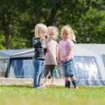 drie kleine meisjes zijn buiten aan het bellen blazen, voor de tent.
