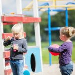 Twee kinders bij het speeltoestel buiten.