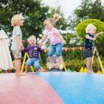 Vier kinderen springen op de trampoline.