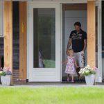 Een vader en dochter komen naar buiten bij het luxe sanitairgebouw.