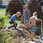 Drie jongens spelen in het zand