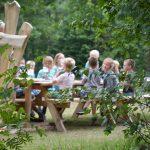 Een groep kinderen aan de picknicktafel buiten.
