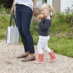 Een meisje met een broodje in haar ene hand en de hand van haar moeder in de andere hand.