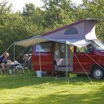 Een rood kampeerbusje met luifel