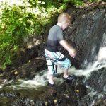 Een jongetje loopt door een watervalletje in een beek