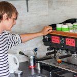 Een jongen maakt een espresso bij Watersportcamping Heeg