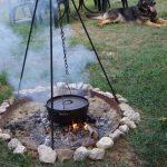 Een dutch oven; driepoot met pan boven het kampvuur.