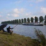Een visser zit aan de kant van het water, een boot vaart voorbij.