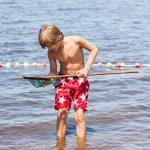 Een jongen met een schepnet en rode zwembroek met witte sterren