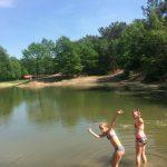 Twee meisjes tot de enkels in het water van het zwemven.