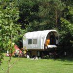 Een huifkar als kampeermiddel op de camping, met een tent daarnaast