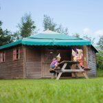 Een aantal kinderen zitten op picknickbank voor de luxe blokhut, dat een kruising is tussen een tent en een bungalow.