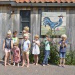 8 kinderen op een rij voor een houten schuurtje met daarop een Blauwe Haan geschilderd.