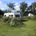 Een kampeerplek met caravan en privé sanitair.