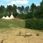 Overzicht van het kampeerterrein met een tipitent en twee Bell tenten.