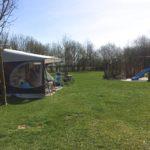 Een caravan met voortent op het kampeerterrein, met rechts in de hoek een speelhuisje