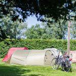 Een groene en rode tent met fietsen ervoor bij Watersportcamping Heeg
