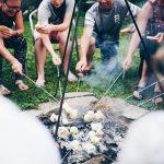 Broodjes bakken aan een stokje boven het kampvuur.