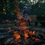 Een kind bij het kampvuur in de schemer.
