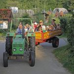 Een groene tractor met aanhangwagen vol met kinderen.