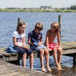 Twee jongens en een meisje op een houten steiger aan het water