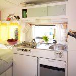 Witte keuken met servies in groen in een caravan