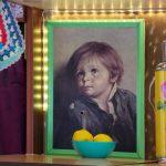 Een groen schilderijlijstje met daarin een afbeelding van een jongetje met tranen
