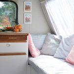 Zitplek naast het keukenblok in een Adria caravan. Gestreepte blauw-witte en roze kussens op de zitbank