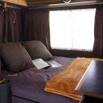 Opgemaakt bed met donker beddengoed, een bruine deken, zwarte kussens en gordijnen