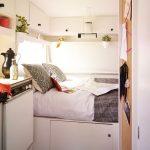 Opgemaakt bed in een wit interieur van een gepimpte caravan van La Gitana