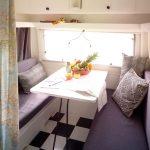 Zithoekje in een caravan met twee banken, zwartwit geblokte vloer en een tafeltje met fruit