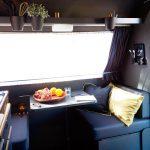 Zithoek in een caravan, met rijke, luxe donkere kleuren en kussens