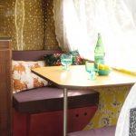 Eethoek in een caravan, met een opklaptafel met glazen, een glas water