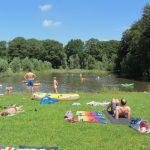 Een grasveldje met zonnende gasten en spelende kinderen in het meer