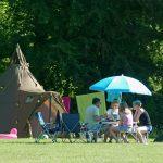 Een groene punt tent met een zitje ervoor met kampeerders onder een blauwe parasol