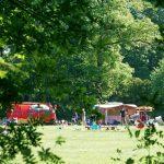 Een rode brandweer camper en vintage caravan op een kampeerveld