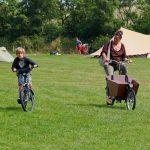 Een bakfiets en jongetje op de fiets over het kampeerveld