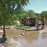 Een ondiepe plas met grote stenen en boomstammen en een speelhuis in het midden, waar kinderen spelen