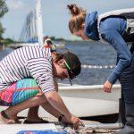Een jongen en een meisje aan de waterkant, bezig met een zeil