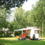 Caravan met luifel op een privé veldje in het groen