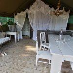 Een luxe safaritent met eettafel en apart slaapgedeelte.